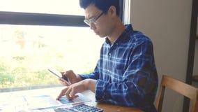 Längd i fot räknat, allvarlig asiatisk affärsman som arbetar med skrivbordsarbete, och räknemaskin för beräkningsdokument affärsr lager videofilmer