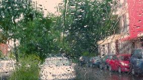 längd i fot räknat av bilfönstret som täckas med regndroppar på gatan lager videofilmer