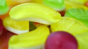 Längd i fot räknat av ljusa smakliga färgglade marmeladgelégodisar roterar arkivfilmer