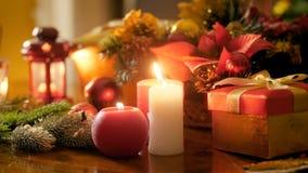 Längd i fot räknat för Closeup 4k av bränningstearinljus och lyktor mot den traditionella kransen och julgåvor och gåvor perfekt stock video