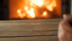 Längd i fot räknat för Closeup 4k av den unga kvinnan i tröja som dricker varmt te vid den brinnande spisen lager videofilmer