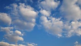 längd i fot räknat 4K av blå himmel med det vita pösiga molnet och guld- ljus på solnedgång- eller soluppgångtid på den molniga d lager videofilmer