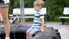 längd i fot räknat 4k av den lilla todlerpojken som sitter på stort tiry på barnlekplats på, parkerar lager videofilmer