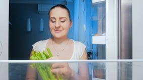 längd i fot räknat 4k av den lyckliga le kvinnan som tar selleri från kylskåpet lager videofilmer