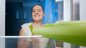 längd i fot räknat 4k av den lyckliga le kvinnan som tar selleri från kylskåpet på natten Begrepp av att banta arkivfilmer