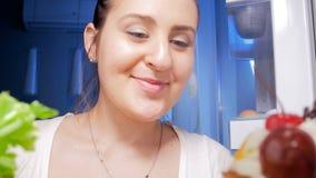 längd i fot räknat 4k av den unga kvinnan som ser inom av kylskåpet på huset och tar selleri arkivfilmer