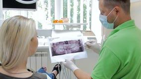 längd i fot räknat 4k av förklarande tänder behandling och uppvisning för tandläkare av röntgenstrålebild till hans patient stock video