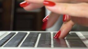 längd i fot räknat 4k Händer för kvinna` s med röd manikyrmaskinskrivning på datortangentbordet Närbild stock video