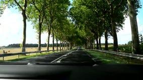 Längd i fot räknat till och med vindrutan på en plan väg i Frankrike och fält med rullar av hö stock video