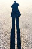 Länglicher Schatten von Person Standing auf der Straße Lizenzfreie Stockfotos