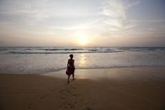 längs att gå för strandflickasolnedgång Royaltyfria Bilder