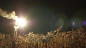 Längs gräset i den mörka astronautet går Sidoplan I hans hand ljusa vita ljusa exponeringar 4K långsam Mo lager videofilmer