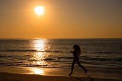 längs strandkvinnligrunning Arkivfoto