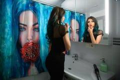 Läppstift för rouge för nätt ung kvinna röd framme av hennes badrumspegel Hårpermanent Duschgardiner med konstmålning Royaltyfri Foto
