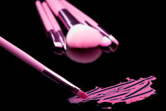 Läppstift med ett borstesmink på svart Royaltyfri Bild