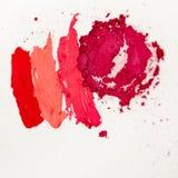 Läppstift- och kantglans, droppar och slaglängder av olika skuggor som skapar olika bilder i makeup arkivbilder