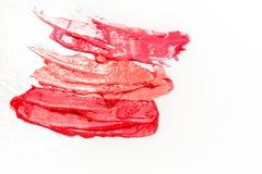 Läppstift- och kantglans, droppar och slaglängder av olika skuggor som skapar olika bilder i makeup royaltyfria foton