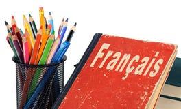 Lär den isolerade franska, läroboken och blyertspennor Royaltyfri Fotografi