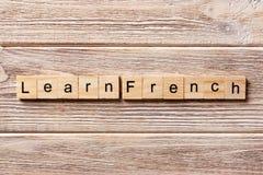 Lär det franska ordet som är skriftligt på träsnittet lär fransk text på tabellen, begrepp royaltyfri foto