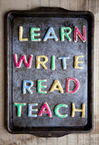 Lär skriver läst och undervisar kakor på bakplåten Arkivfoton