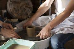 Lära att modellera från lera vid en förlage på ett hjul för keramiker` s Royaltyfri Fotografi