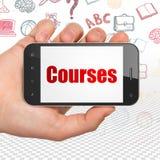 Lära begrepp: Hand som rymmer Smartphone med kurser på skärm Fotografering för Bildbyråer