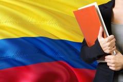 Lära colombianskt språkbegrepp Anseende för ung kvinna med den Colombia flaggan i bakgrunden Lärare som rymmer böcker, apelsin arkivbild