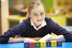 Lära för ord som stavas i träkvarter med eleven bakom Arkivfoto