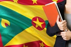 Lära grenadiskt språkbegrepp Anseende för ung kvinna med den Grenada flaggan i bakgrunden Lärare som rymmer böcker, apelsin royaltyfri bild