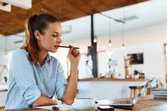 Lära och att studera Kvinna som använder bärbar datordatoren på kafét som arbetar