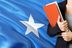 Lära Somalian språkbegrepp Anseende för ung kvinna med den Somalia flaggan i bakgrunden Lärare som rymmer böcker, apelsin royaltyfria foton