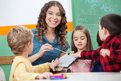 Lärare And Children Playing med xylofonen in royaltyfri bild