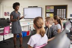 Lärare With Digital Tablet som talar för att fodra av högstadiumstudenter som sitter vid skärmar i datorgrupp arkivfoto