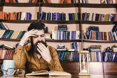 Lärare eller student med skägget som studerar i arkiv Man på att gäspa framsidaläseboken som studerar, bokhyllor på bakgrund Arkivbild