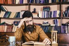 Lärare eller student med skägget som studerar i arkiv Man på den koncentrerade framsidaläseboken som studerar, bokhyllor på Fotografering för Bildbyråer