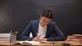 Lärare för ung dam som kontrollerar schoolchildrensuppgifter, ockupation, skrivbordsarbete arkivfilmer