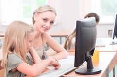 Lärare förklarar uppgiften på datoren Royaltyfri Foto