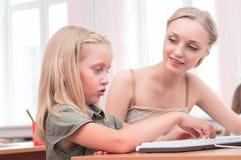 Lärare förklarar uppgiftsschoolgirlen Fotografering för Bildbyråer