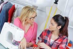 Lärare Helping College Students som studerar mode och design arkivfoton