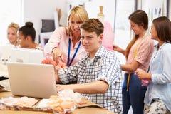 Lärare Helping College Students som studerar mode och design royaltyfri bild