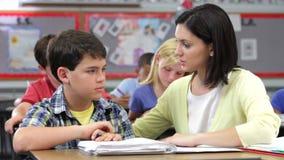 Lärare Helping Male Pupil i grupp arkivfilmer