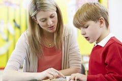 Lärare Helping Male Pupil med läsning på skrivbordet arkivfoto