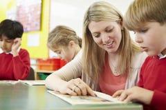 Lärare Helping Male Pupil med läsning på skrivbordet royaltyfri foto