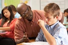 Lärare Helping Male Pupil som studerar på skrivbordet i klassrum arkivfoto