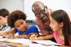 Lärare Helping Pupils Studying på skrivbord i klassrum Royaltyfria Bilder