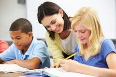 Lärare Helping Pupils Studying på skrivbord i klassrum arkivfoto