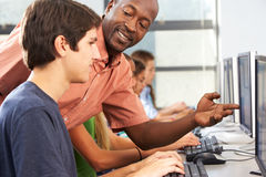 Lärare Helping Students Working på datorer i klassrum royaltyfria bilder