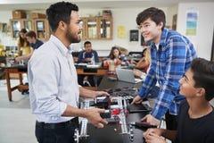 Lärare With Male Pupils som bygger det Robotic medlet i vetenskapskurs fotografering för bildbyråer