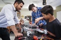 Lärare With Male Pupils som bygger det Robotic medlet i vetenskapskurs arkivbild