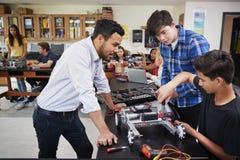 Lärare With Male Pupils som bygger det Robotic medlet i vetenskapskurs royaltyfri fotografi